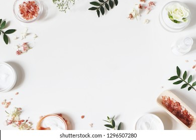 Styled beauty frame, web banner. Skin cream, tonicum bottle, dry flowers, leaves, rose and Himalayan salt. White table background. Organic cosmetics, spa concept. Empty space, flat lay, top view. - Shutterstock ID 1296507280