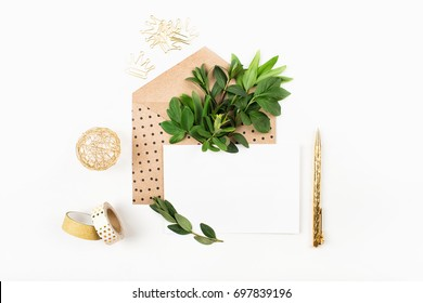 Styled desk with envelope, blank card, composition of green leaves and gold office stuff. Flat lay.