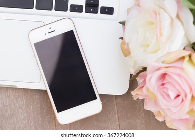 styled desktop with modern phone, pc keyboard and flowers