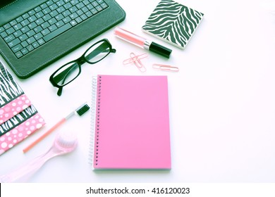 A styled desktop in pink and black on a white background with a keyboard, glasses, lipstick, facial brush, paperclips, coaster and a pink notebook.