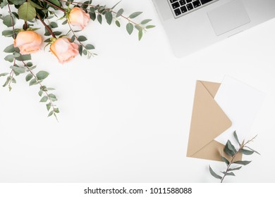 Styled feminine desk workspace with pink roses, laptop computer, green leaves eucalyptus, envelope and white note card. Top view and flat lay of table office desk.