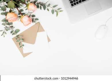 Styled feminine desk workspace with pink roses, laptop computer, green eucalyptus leaves, mouse, envelope and white note card. Top view and flat lay of table office desk.