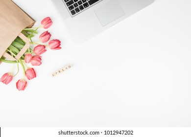 Styled feminine desk workspace with pink tulips, laptop computer and spring letters. Top view and flat lay of table office desk.