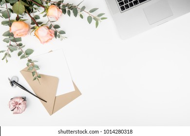 Styled feminine desk workspace with pink roses, laptop computer, green eucalyptus leaves, calligraphy nib, present box, envelope and white note card. Top view and flat lay of table office desk.