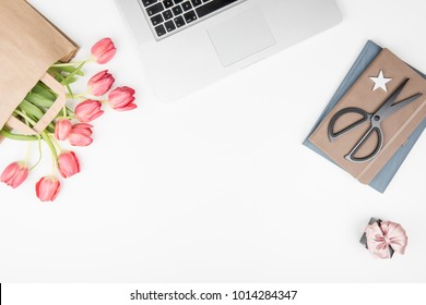 Styled feminine desk workspace with pink tulips, laptop computer, notebooks and present box. Top view and flat lay of table office desk with copy space.