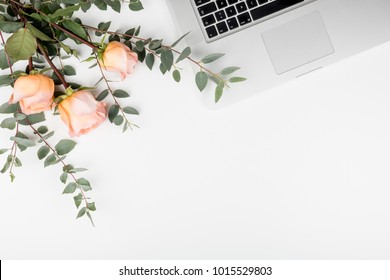 Styled feminine desk workspace with pink roses, laptop computer and green leaves eucalyptus. Top view and flat lay of table office desk with copy space.