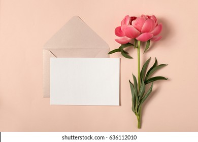 Styled feminine flat lay on pale pastel pink background, top view. Minimal woman's desktop with blank page mock up, open envelope and peony flower, Creative concept, empty greeting card
