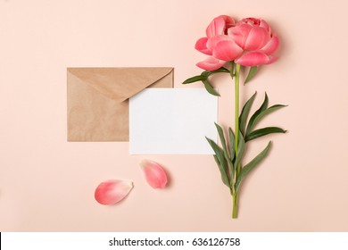 Styled feminine flat lay on pale peach background, top view.Minimal woman's desktop with blank page mock up, craft envelope, peony flower, petals. Creative concept, greeting card template. Horizontal