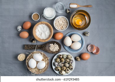 Styled flatlay with baking ingredients top view on cloth on the table. Different kinds of eggs, powder, sugar and cooking items.