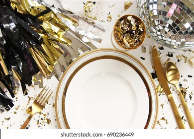 Styled glamorous black, silver and gold table setting with modern plates, silverware, disco ball and confetti. White copy space.