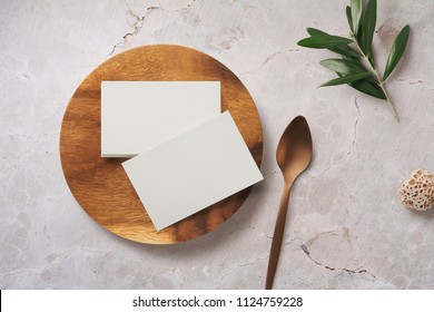 styled minimalist food or restaurant related branding mock-up with stack of business cards on a wooden plate and olive twig on a blush marble background - top view / flat lay