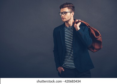 Confident young handsome man in glasses holding bag and looking away a870c1604ab2