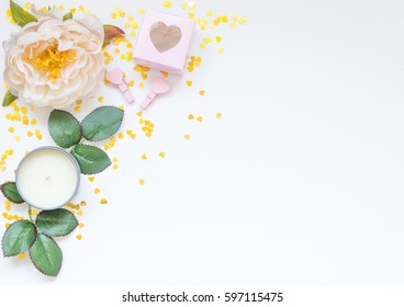 Styled photo with flowers, candle, pink accessories and golden hearts