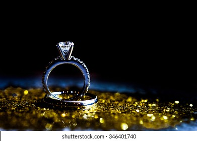 A styled silhouette of a diamond engagement ring and a man's wedding band.