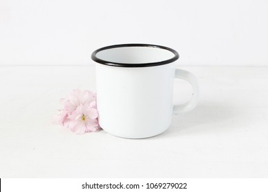 Styled stock photo. Feminine still life composition with blank white metal coffee enamel mug and pink Japanese cherry blossoms, flowers on white table background. Spring rustic scene, product mockup.