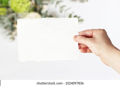 Styled stock photo. Feminine wedding, birthday greeting card mockup scene with woman's hand in holding blank paper card. Blurred floral background. Empty space. Picture for blog or social media.