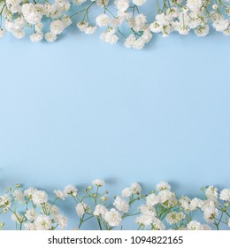 Styled stock photo. Feminine wedding desktop mockup with baby's breath Gypsophila flowers on  blue background. Empty space. Floral frame, web banner. Top view. Square icture for blog or social media.