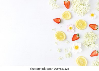 Styled stock photo. Spring or summer fruit composition. Sliced lemons, elderflowers, strawberries and wild roses isolated on white wooden table background. Food pattern. Flat lay, top view.