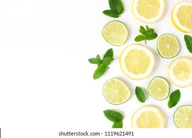 Styled stock photo. Summer herbs and fruit composition. Lime, lemon slices and fresh green mint leaves isolated on white table background. Juicy food pattern. Empty space. Flat lay, top view.