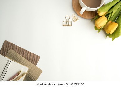 Styled stock photography white office desk table with blank notebook, keyboard, macaroon, supplies and coffee cup. Top view with copy space. Flat lay.