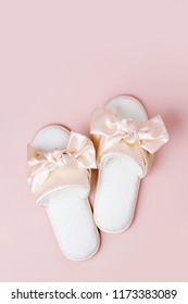 Stylid female slippers with bow on pale pink  background. Flat lay, top view
