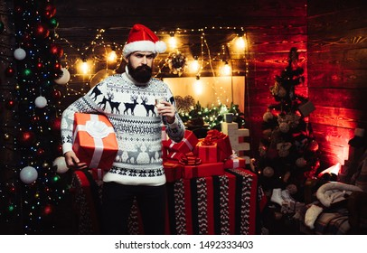 Styling man with a long beard posing on the wooden background. Delivery gifts. Santa Claus wishes Merry Christmas