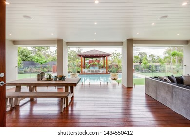 A stylish 4 seater wooden bench and snack table with an angled sofa set, overlooking the pool and patio area.