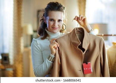 stylish 40 years old woman in white sweater and skirt showing beige coat with sale price tag in modern fashion showroom.
