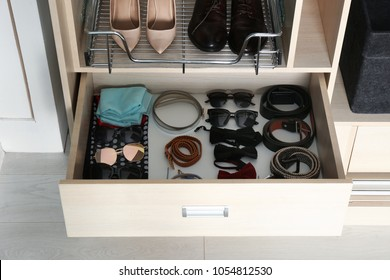 Stylish accessories in drawer of wardrobe closet