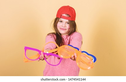 Stylish accessory. Feeling confident with accessories. Girl cute child wear cap or snapback hat hold eyeglasses beige background. Modern fashion. Little girl wearing bright baseball cap. Hat or cap.
