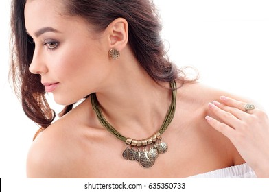 Stylish accessory on woman. Necklace with choker on neck and earring with finger ring. Close-up studio isolated shot of spring jewelry collection