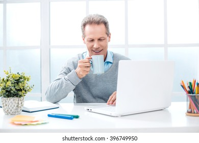 Stylish adult businessman while working day in office. Businessman with laptop, drinking coffee and smiling. Office interior with big window