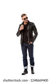 stylish adult man in leather jacket with hand in pocket drinking coffee to go isolated on white