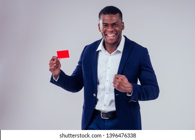 stylish african american in costume black pants and jacket with a big shirt collar holding red credit plastic card in studio on white background, badge my name is