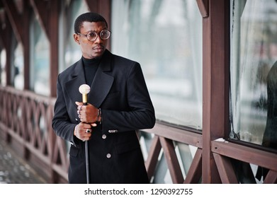 Stylish african american gentleman in elegant black jacket, holding retro walking stick as cane flask or tippling cane with golden diamond ball handle. Rich fashionable afro man.
