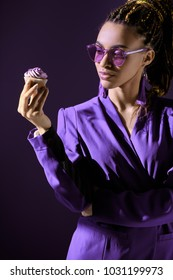 Stylish african american girl in ultra violet jacket and sunglasses looking at cupcake, isolated on dark purple