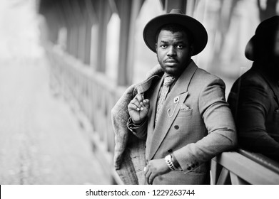 Stylish African American man model in gray coat, jacket tie and red hat posed at foggy weather street. Black and white photo.