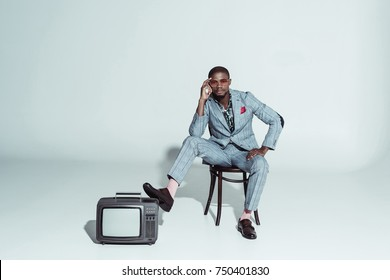 Stylish african american man posing on wooden chair with one leg on a retro television