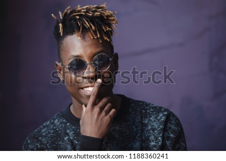 66372db2717 Stylish african american man rapper wear cool glasses at violet wall  background