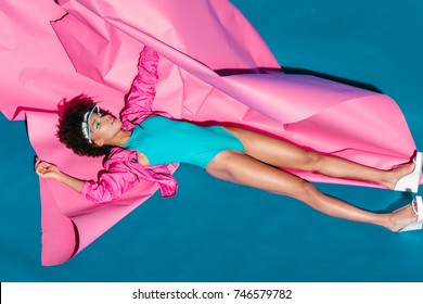 stylish african american model posing with pink paper for fashion shoot in 80s style