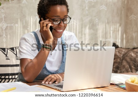 ad458a8cce Stylish African American woman calls on smart phone looks in laptop computer
