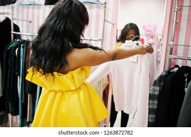 Stylish african american woman at yellow dreess posed at pink shop and chooses clothes against mirror.