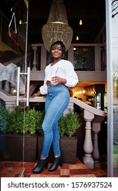 Stylish african american women in white blouse and blue jeans posed at cafe with caramel latte.