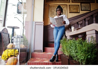 Stylish african american women in white blouse and blue jeans posed at cafe read menu.
