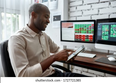 Stylish african businessman, trader sitting by desk in front of multiple monitors and using his smartphone to check charts while working in the office. Stock trading, people concept.