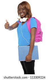 Stylish african college girl showing thumbs up to camera. All on white background