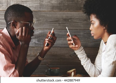 Stylish African couple using cell phones totally absorbed in online life, with obsessed look, not talking to each other, using Wi-Fi at a coffee shop, facing one another. Internet addiction concept