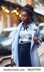 Stylish African girl in the blue coat on the street with bokeh in the background