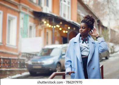 Stylish African girl in the blue coat in the style fashion on the streets with bokeh and cars in the background