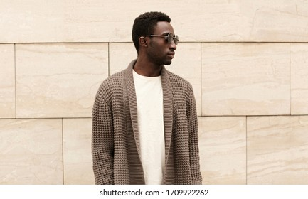 Stylish african man looking away wearing brown knitted cardigan, sunglasses on city street over brick wall background